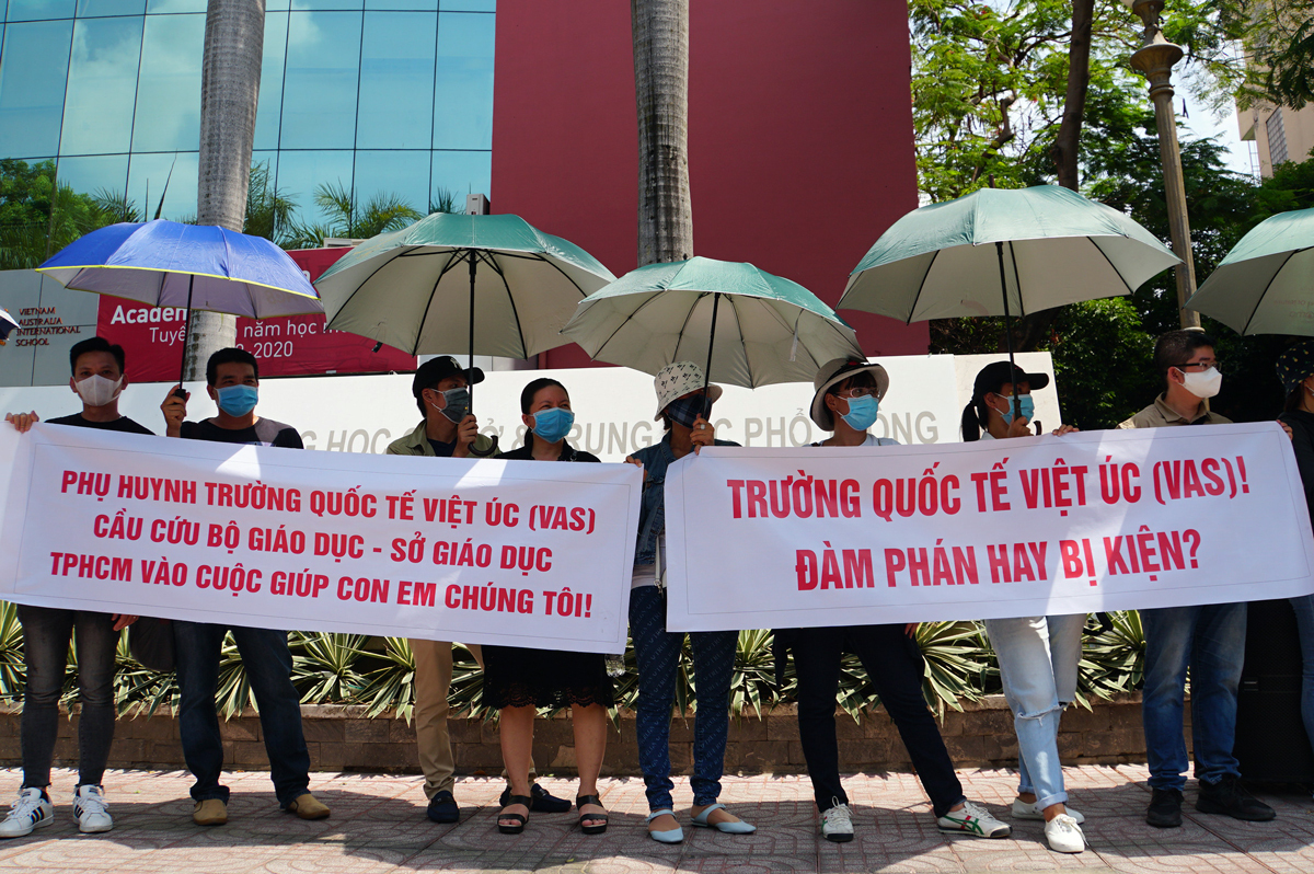 A group of parents comes to a VAS facility in HCMCs District 10, sporting banners to protest the schools tuition policies during the period where students stayed home due to the Covid-19 pandemic, May 14, 2020. Photo by VnExpress/Manh Tung.