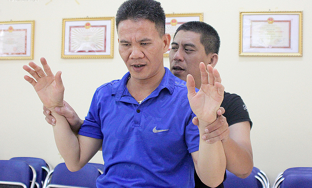 Cuong (behind) shows a learners how to move his hands. Photo by VnExpress/Thuy Quynh.