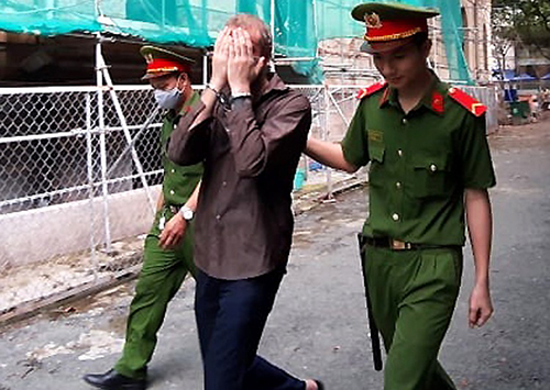 Police escort Adam Michael Nowicki as he leaves the court in Ho Chi Minh City July 9, 2020. Photo by VnExpress/Anh Duy