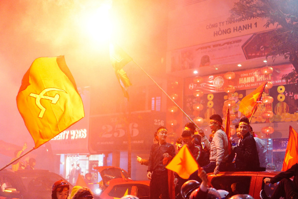 Football fans fly the Communist Party flag and set off flares on Hue Street. Photo by VnExpress/Dung Luong