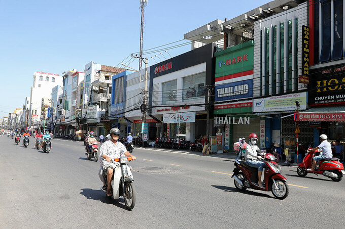 Motorbike drivers travel on Hung Vuong Street in Da Nang City without shades of green trees. Photo by VnExpress/Nguyen Dong.
