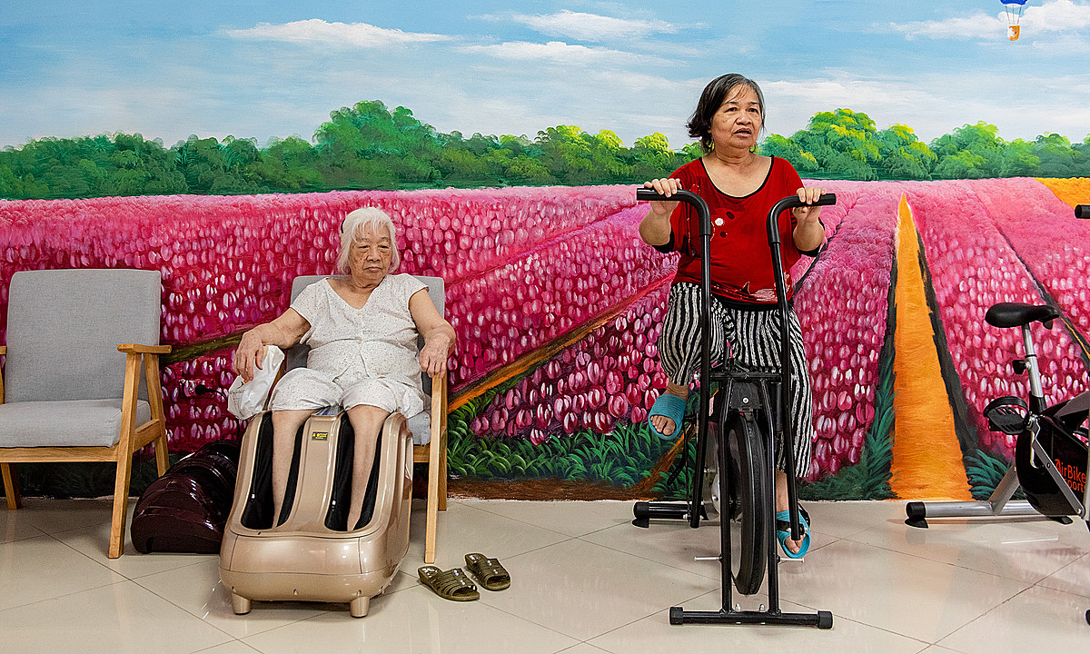 Nguyet (R) works out on a stationary bicycle. Photo by VnExpress/Thanh Hue.
