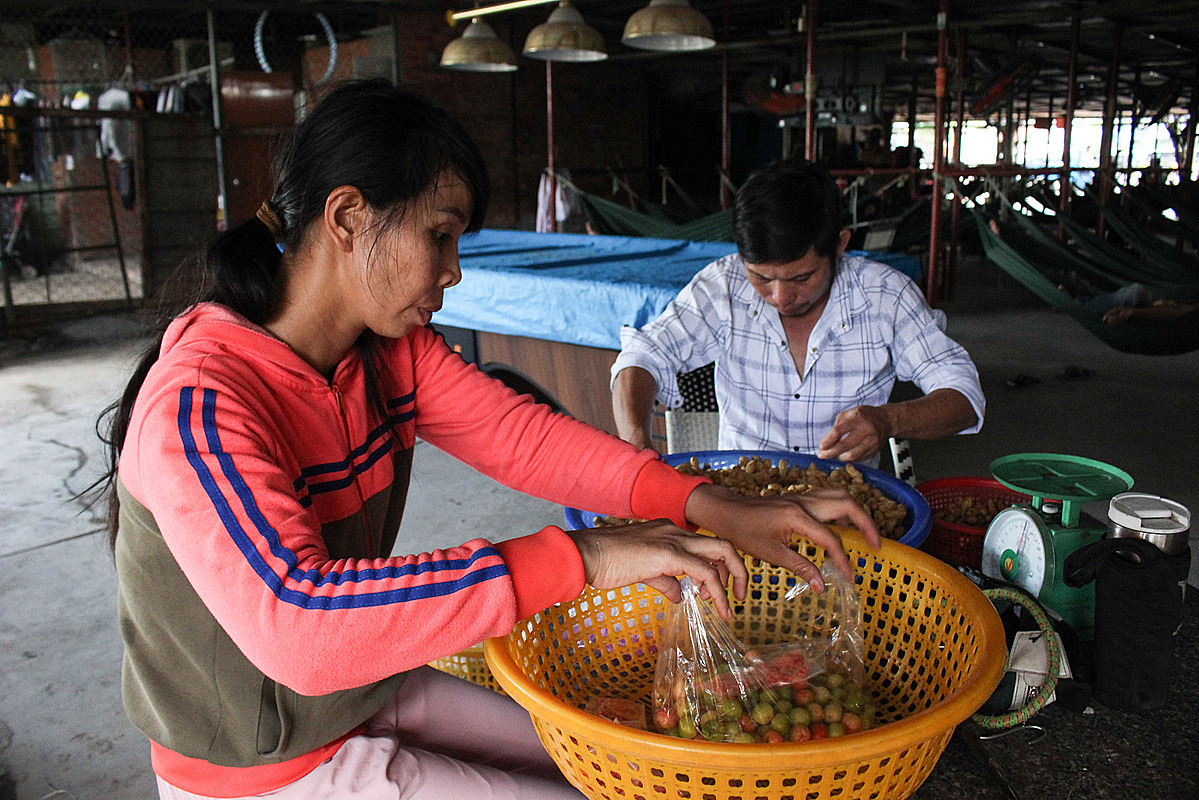 Loan and Hung prepare snacks to sell to local drinkers. Photo by VnExpress/Diep Phan.