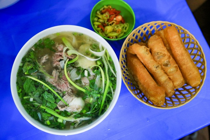 A bowl of pho with beef next to crunchy bread, a typical side dish at Tuans shop on Le Van Linh Street, Hanoi. Photo acquired by VnExpress