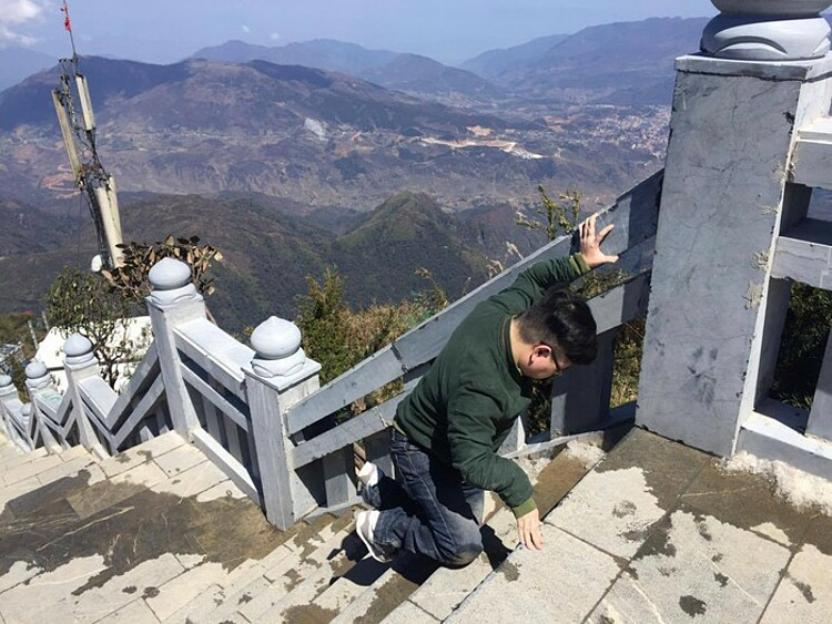 Anh uses his knee to climb the staircase leading to top of Mount Fansipan, the highest peak in Indochina. Photo courtesy of Anh.