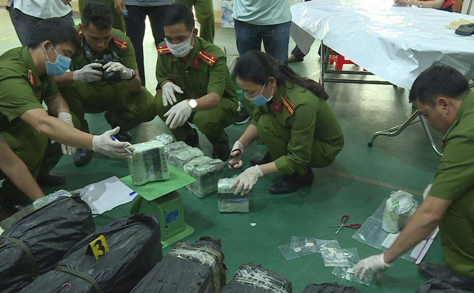 Police officers put packs of meth on a scale, July 20 2020. Photo by VnExpress/Thu Ha.