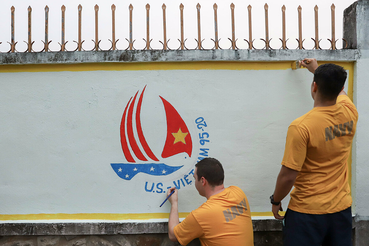 American soldiers from aircraft carrier USS Theodore Roosevelt paints the icon of U.S. and Vietnams 25th diplomatic relationship anniversary on the wall of a charity center in Da Nang during a visit on March 5, 2020. Photo by VnExpress/Nguyen Dong.