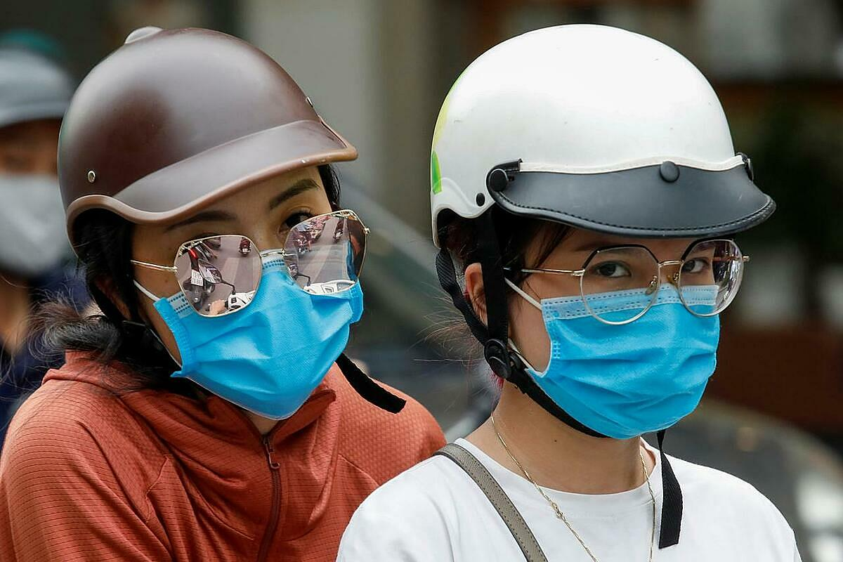 Women wear protective masks as they ride in a street, during the Covid-19 outbreak, in Hanoi, July 27, 2020. Photo by Reuters.
