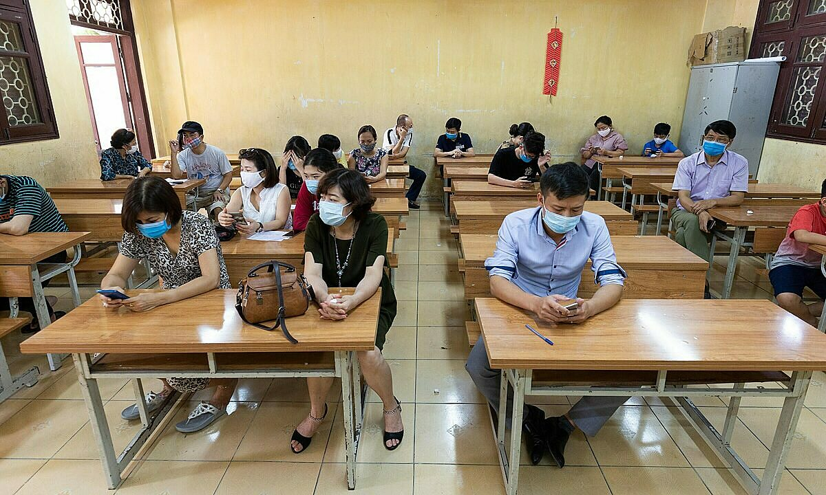 Da Nang returnees in Hanoi are waiting for their Covid-19 tests in a classroom at Thanh Cong Secondary School on the morning of July 31, 2020. According to Dr. Khong Minh Tuan, Deputy Director of theHanoiCenter for Disease Control (CDC), as of midday of July 31, 21,732 people in the city have been tested.