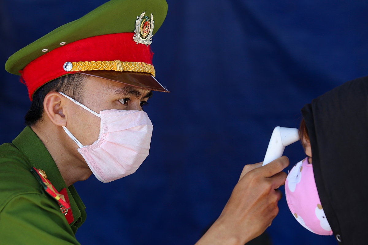 A police officer in Quang Nam Province checks the body temperature ofa woman arriving from Da Nang, July 29, 2020. Photo by VnExpress/Dac Thanh.