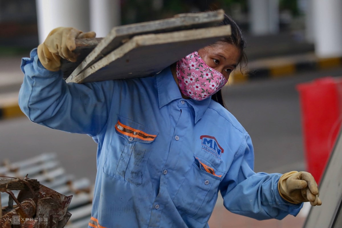 A worker carries a stack of plates on her shoulders.