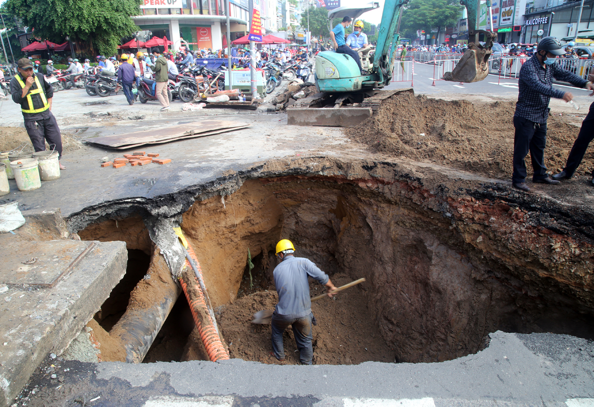 Workers from the  HCMC Urban Drainage Co. Ltd fix the sinkhole on the morning of August 7, 2020. Photo by VnExpress/Dinh Van