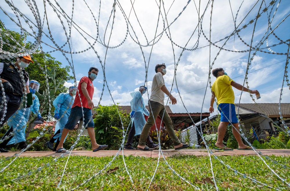 Foreign migrant workers wearing face mask walk to do the Covid-19 screening test in Malaysia in May 12, 2020. Photo by Shutterstock/Abdul Razak Latif.
