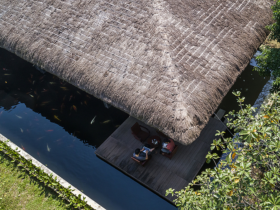 The sheet steel roof is covered by a thatched layer that is a signature architecture in many rural areas in Vietnam. It also helps the building integrated into nature and the surounding area.