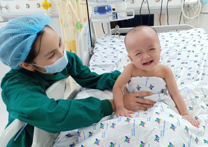 Hoang Dieu Nhi laughs with a nurse holding her at the HCMC Childrens Hospital, August 2020. Photo by VnExpress/Phuong Vu.