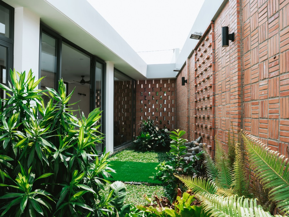 A tropical garden lurks behind the brick wall. Photo by Cung Vit.