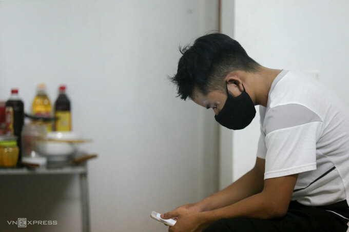 Alang Dens roomate using his smartphone. Photo by VnExpress/Gia Chinh.