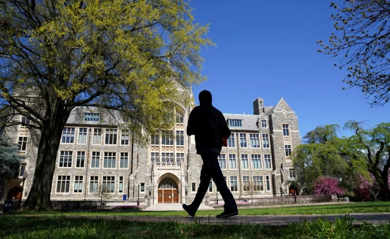 A man walks on an empty campus green at Georgetown University, closed weeks ago over the Covid-19 pandemic. Photo by Reuters//Kevin Lamarque.