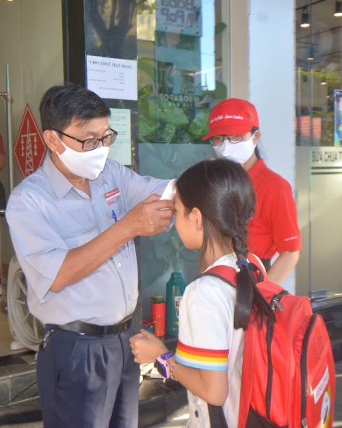 An employee at an English center on Nguyen Van Linh Street checks the temperature of students before allowing them in. Hand sanitizers are placed at the front door.