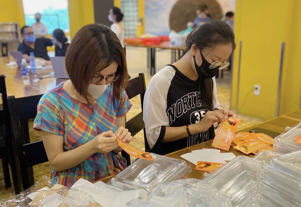 Bich Huong (left) and a volunteer sticks Da Nang Kitchen logo on meal boxes. Photo by VnExpress/Hoang Phuong