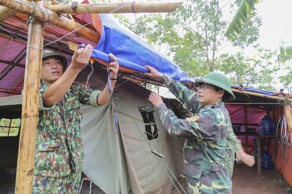 Senior Lieutenant Nguyen Van Binh (L) fix a canvas to protect the camp from the rain. He and the others spend their own money buying the new canvas.