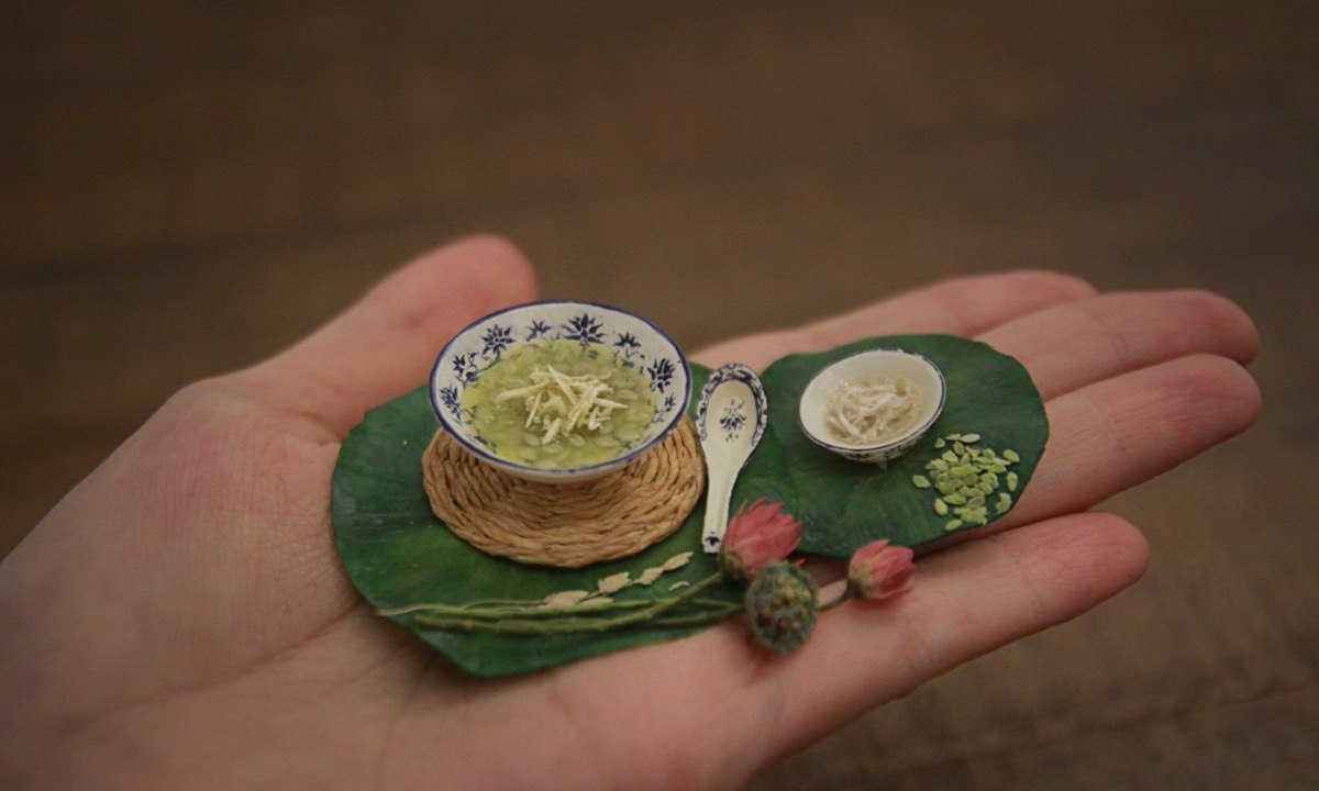 Che com, a dessert made of young sticky rice flakes, a culinary specialty in Hanoi. It is served with coconut flakes, put on a lotus leaf. According to An, this is the most complicated replica as the bowl and spoon with hand-drawing patterns took her a long time to create.