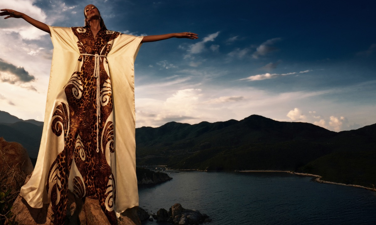 The beauty queen wears an oversized dress with nature-inspired patterns.