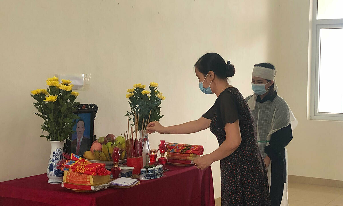 A person in the quarantine facility came to burn incense at a newly set up altar for Hoats father. Photo by VnExpress/Hoang Phuong.