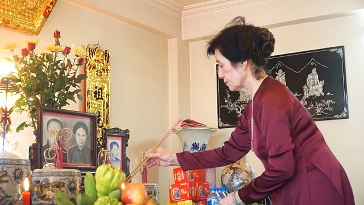 Le Thi Bich Huong makes offering at home before attend the virtual ceremony at the cementary. Photo by VnExpress/Nguyen Ngoan.