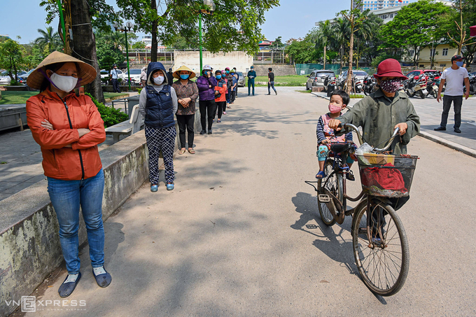 People wait in line to receive rice support in Hanoi, April 2020. Photo by VnExpress/Giang Huy.
