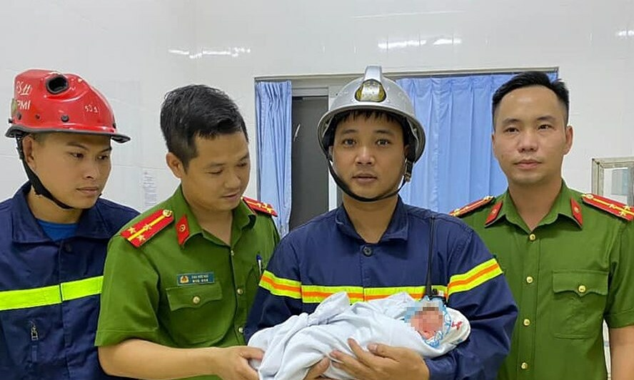 Major Nguyen Dang Manh, deputy head of Hanois Gia Lam District Police, holds a newborn baby he helped rescue from a gap between two houses, August 18, 2020. Photo courtesy of Gia Lam District police.