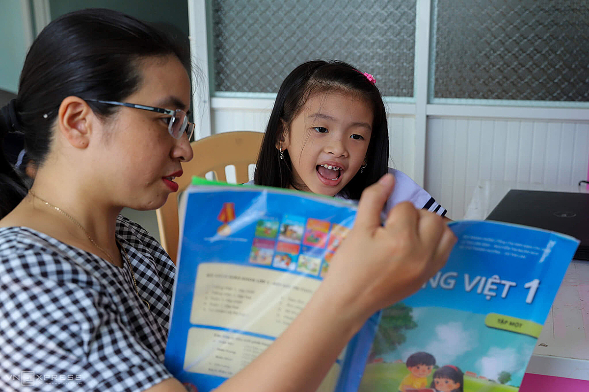Tran Thi Huong, 32, living in an apartment of Hoa Khanh Industrial Zone in Da Nangs Lien Chieu District, teaches her 6 years old daughter, Trinh Tran Nguyen An, to practice reading at home since there were no opening ceremony.I want to give her the feeling of attending class on the first day of school, said Huong, who is a teacher.