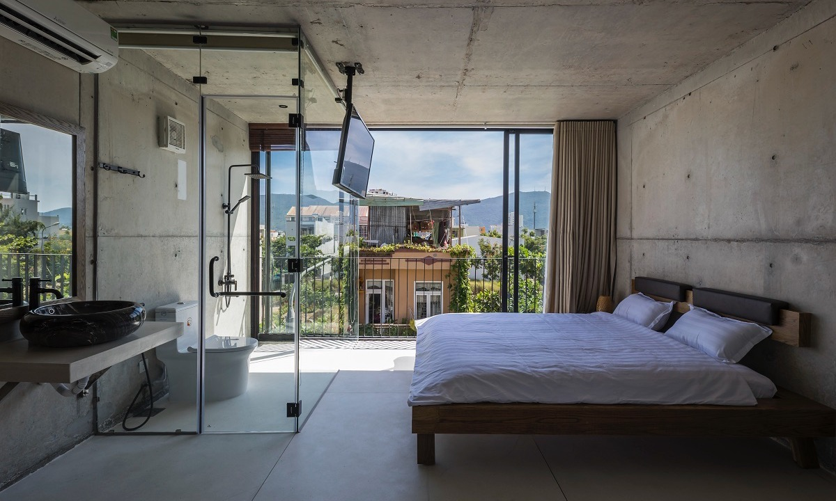 According to architects, the crystal clear bathroom and restroom make the bedroom look more spacious. The window with a curtain can protect homeowners privacy while the glass walls are well constructed to prevents water from splashing and causing smells in the bedroom.