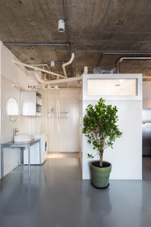 The bathroom is located next to the restroom, with a crystal clear curtain separating it from the outside. Photo by Hiroyuki Oki.