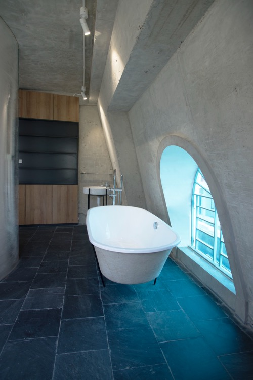 On the fifth floor, owners decide to have a bathroom on a concrete floor with a window allowing them to have more natural light and have a better view while showering. The doorless bathroom is separated from the bedroom by a polycarbonate wall.