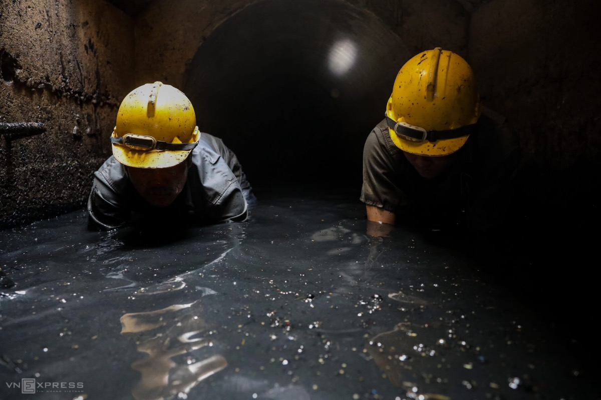 Inside the pits, 3 meters underground, the father and son have to wait for the rain to finish so the water level would decrease, making it easier for their job. Having their faces close to the filthy water, the duo use buckets to take out mud and stinky sewage.