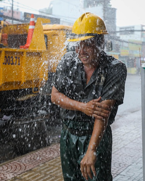 Son showers himself in the rain. Taking a shower on the streets is not a rare thing among sewer workers, who normally shower themselves up to five times after their shift.