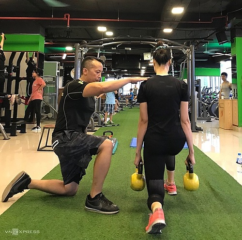 Tran Quang Anh trains a member at a gym in Tay Ho district, Hanoi. Photo courtesy of Anh.
