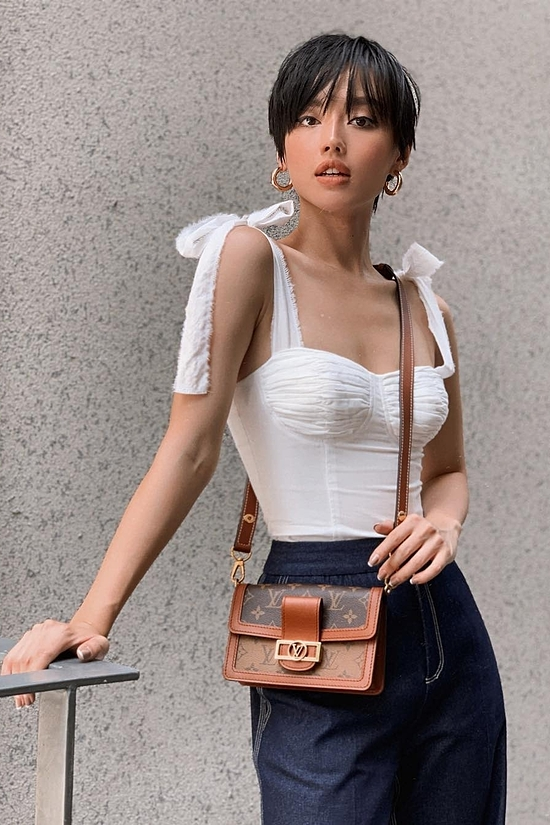 Apart from dresses, shirts were also designed with a modern touch of corset. Model Khanh Linh combine a corset white shirt with a jeans to show off her modern look.