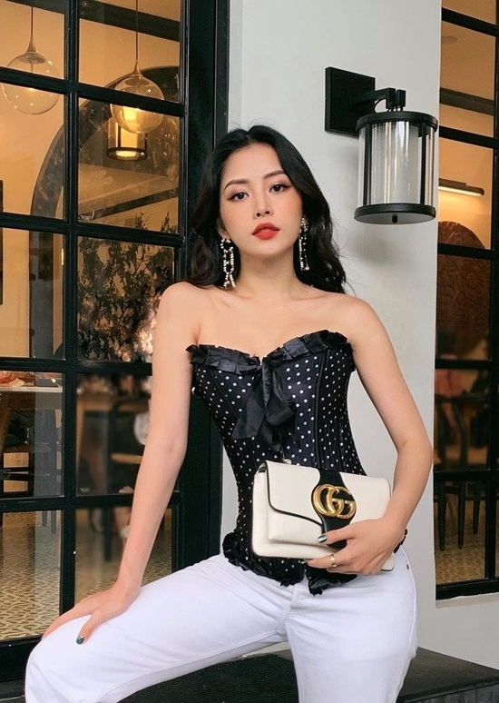 Singer Chi Pu opts for a black corset top with white trousers and a Gucci handbag.