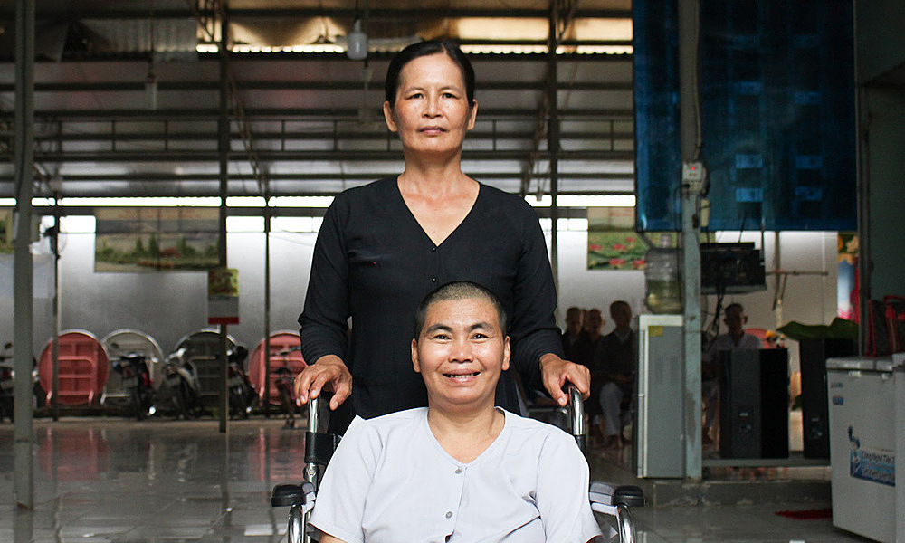 Nguyen Thi Bay (sitting), 40, has a mental disorder and has been homeless since she was a child. Photo by VnExpress/Diep Phan.