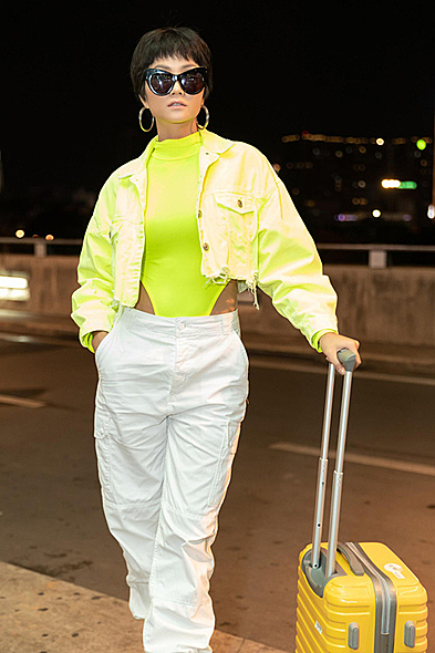 Miss Universe Vietnam 2018 HHen Nie hit the airport with a neon swimsuit and jacket, giving her a colorful look. Bikinis and one-piece swimsuits have become daily styles of many models and celebrities worldwide since 2019,  several fashion houses included swimwear with their collections and made them becomes streetwear.