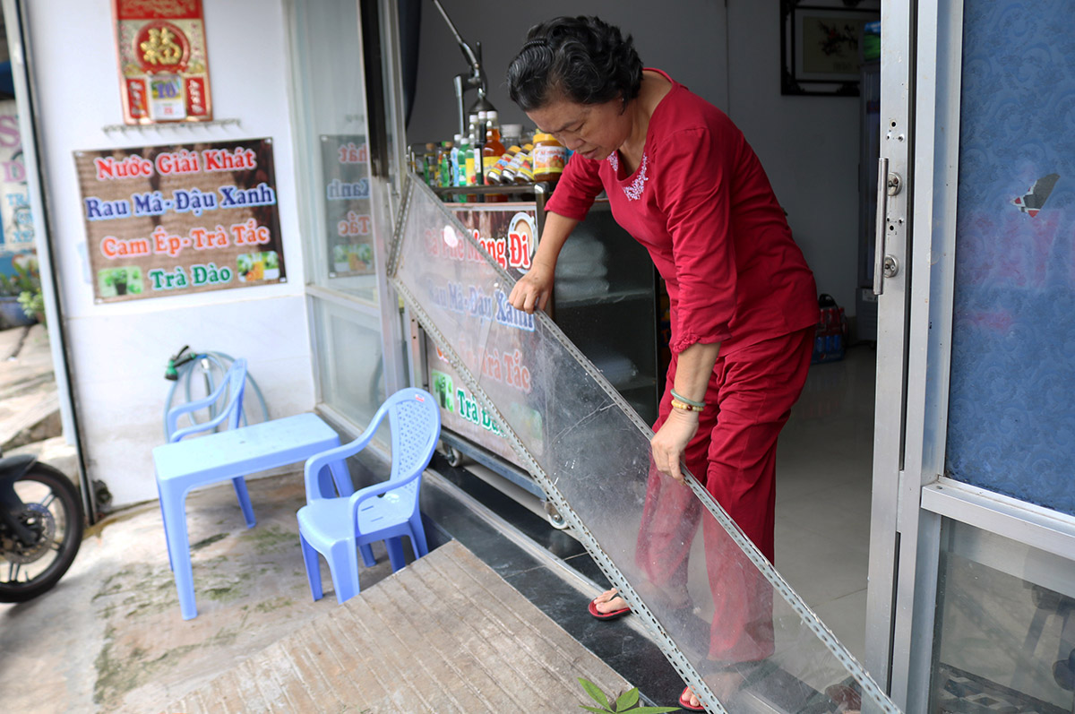Dang Thi Huong removes a sheet of plastic she uses to prevent flood water from going in her house in HCMCs Thu Duc District, September 2020. Photo by VnExpress/Gia Minh