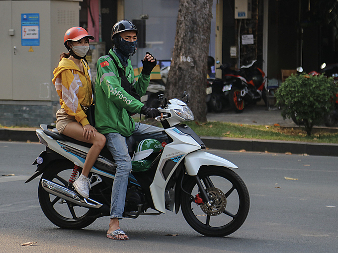 A motorbike taxi driver wears a mask while driving. Photo by VnExpress/Hoang Huy.