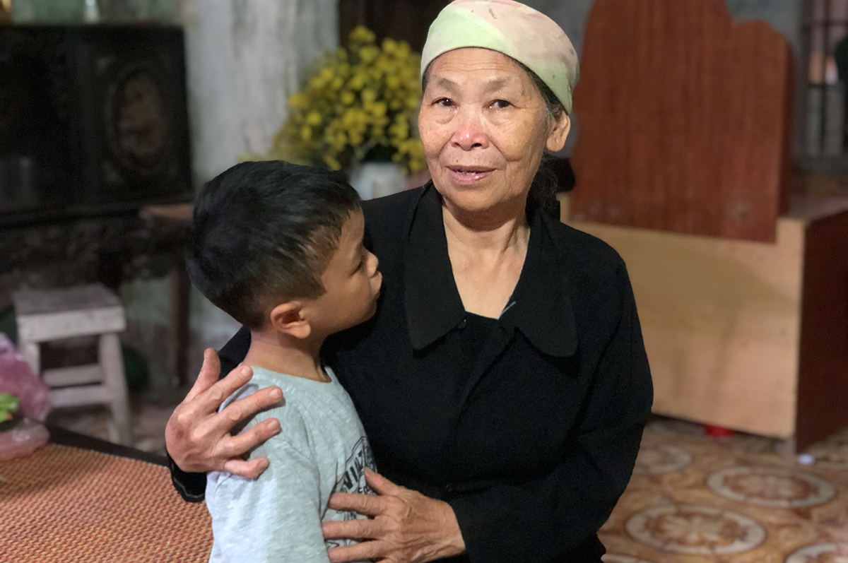 9-year-old Nguyen Huu Hung in the arms of his maternal grandmother, 73-year-old Nguyen Thi Hanh, in Hung Yen Province. Photo by VnExpress/Pham Du.