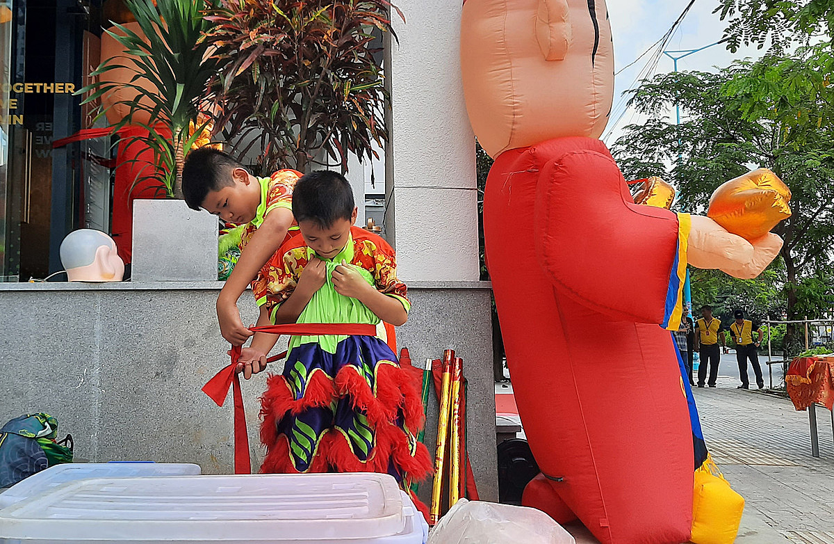 Two members of the Long Nhi Duong prepare for performance. Children in the team often perform small unicorns, or be a local grandfather
