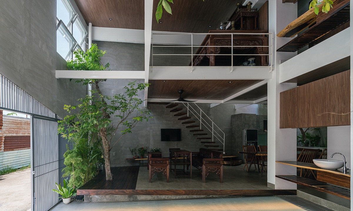 The parking lot, living room, dining room, kitchen, toilet, and one bedroom are on the first floor. Trees are planted in many spaces, while the brown shades of the furniture create a sense of coziness in the house of a three-generation family.