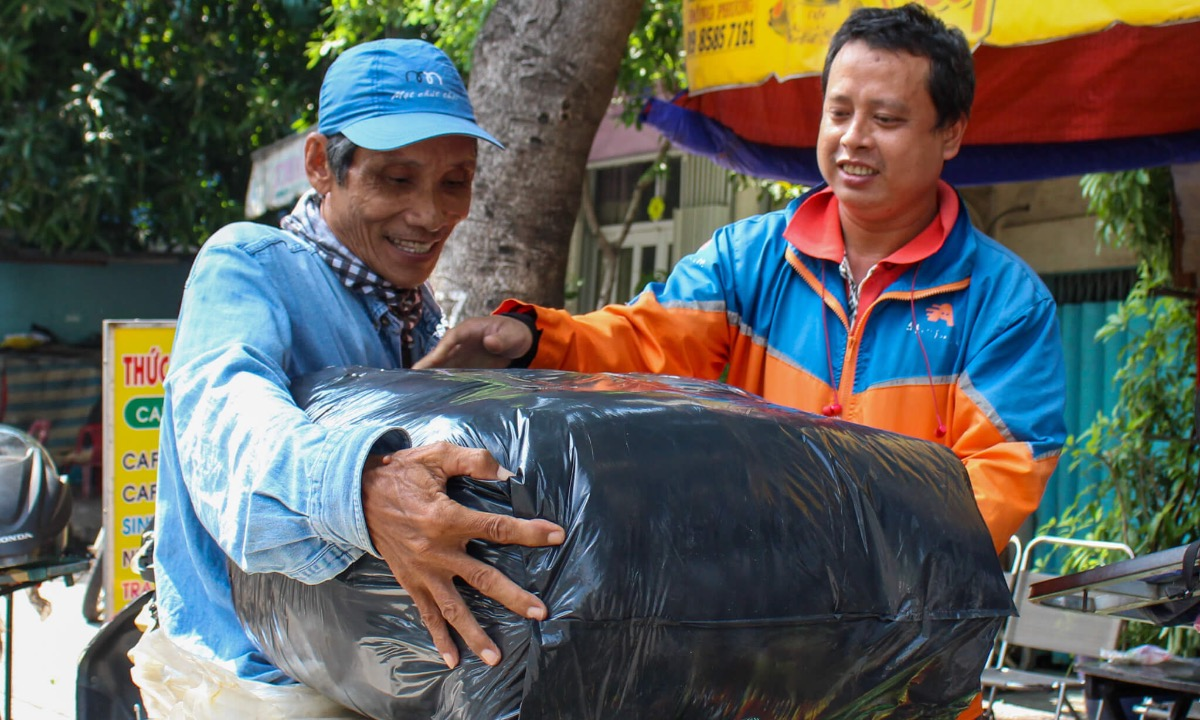 Lam Ngoc (orange shirt), a delivery man from Binh Thanh District, usually helps Long. When he sees the man have no client, he talks with other colleagues to share their orders with Long so he can earn more money.  We are not disabled but this job is still hard for us, so Long must feel the same. We all love him, Ngoc maintained.