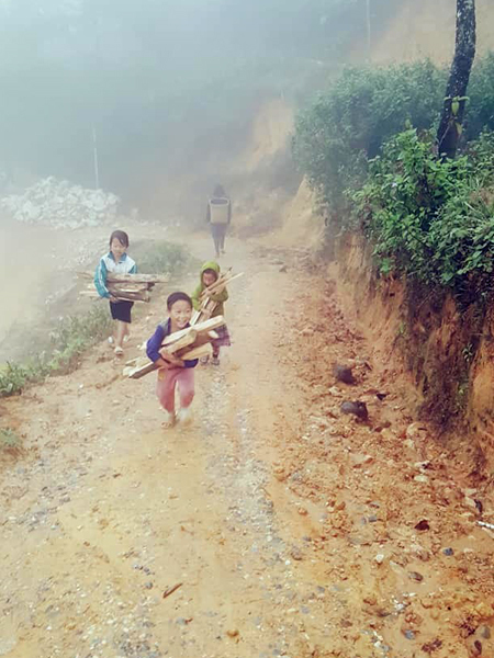 Local children help An carry firewood. Photo courtesy of Tam An.