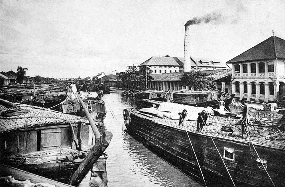 Boats in front of a factory in Cho Lon area, which was formed between the 17th and 19th centuries when ethnic Chinese and their offspring settled here and built a bustling area. When the French dominated the country, Cho Lon was a town distinct from Saigon. The two were combined in 1956. Currently it is Ho Chi Minh Citys Districts 5 and 6.